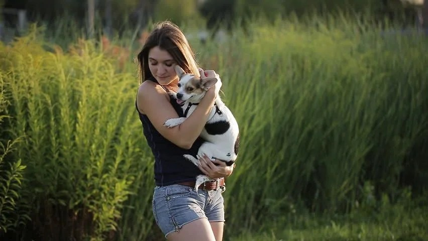 Young Beautiful Woman Blowing A Kiss To Her Dog At The