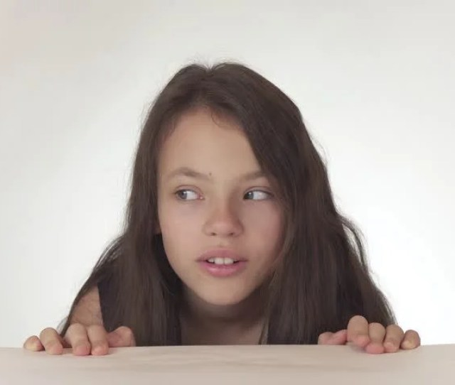 Beautiful Happy Naughty Teen Girl Having Fun Getting Out From Under The Table And Hiding Back On A White Background Stock Footage Video