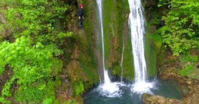 A Tropical Waterfall Flows Through A Dense Rainforest In ...