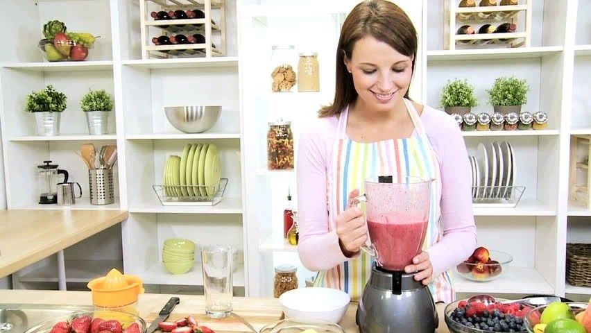 This is a woman learning to use a blender to make a smoothie.