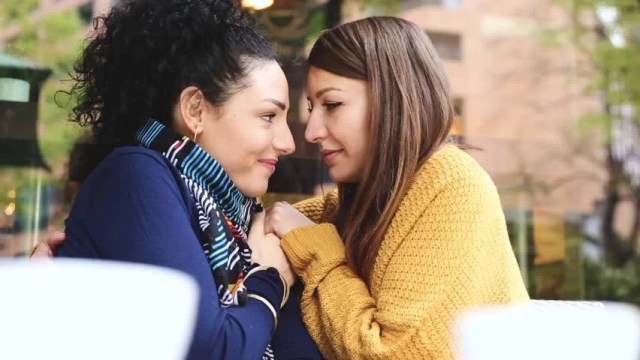 Lesbian Couple At A Cafe Two Young Women Are Having A Coffee Together Talking Cuddling And Give Each Other A Kiss Candid Situation With Real People