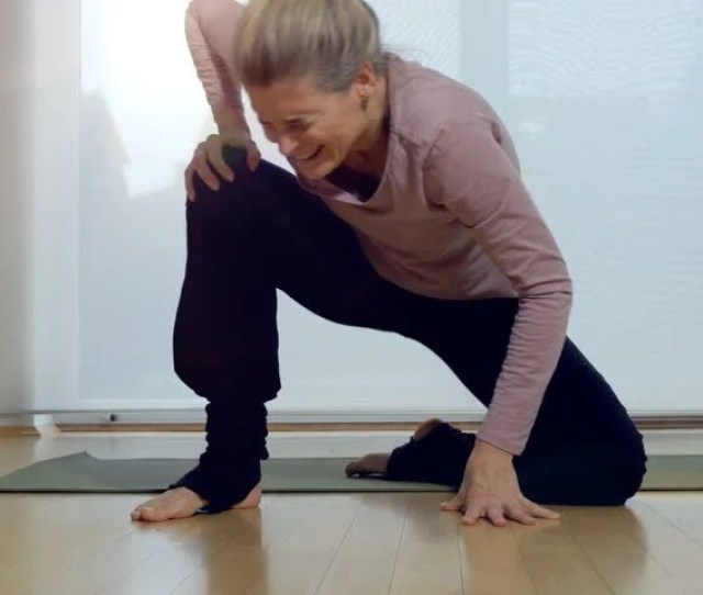 Woman Cringing In Pain After Attempting To Stand Up Following Yoga Exercise Full Length