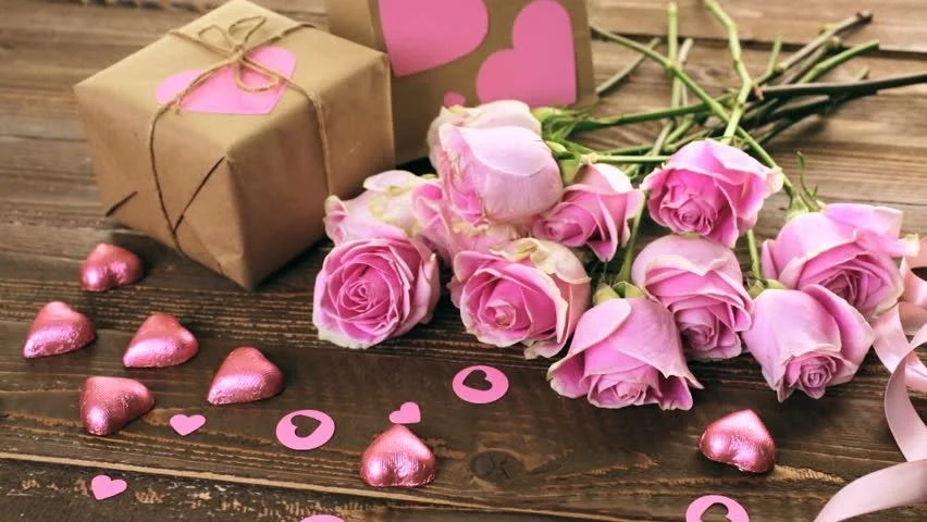 Stock video of romantic valentine  39 s day candles and flowers     hd00 14Pink roses and gift wrapped in recycled paper on rustic wood table