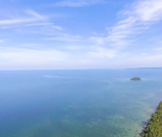 Slow Aerial Orbit Over Crystal Clear Lake Michigan During Late Summer Early Fall Foliage
