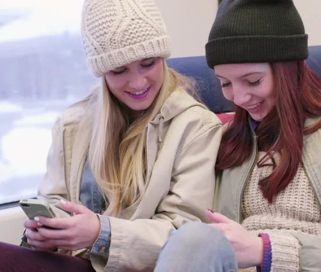 Two Happy Chatty Teen Girls Play With Their Smartphones Their Train Comes To A Stop They Look Out Window To Check If It Is Their Stop Its Not