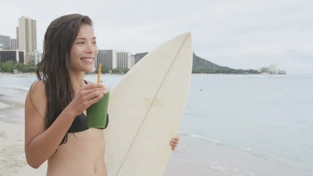 Slow Motion Video Of Young Woman In Bikini Having Healthy Juice She Is Holding Surf Board While Looking Around At Beach Sensuous Female Is Smiling While