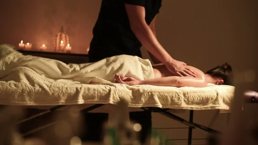 A Big Guy Massage Therapist Does A Massage For A Young Girl Lying On The Sofa Face Down In A Dark Office With Candles In The Background