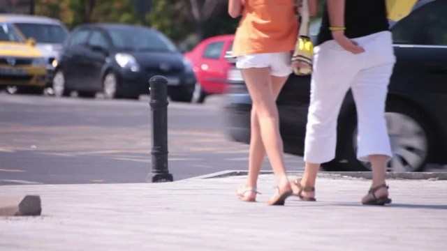 Attractive Walking Young Adult Woman Hot Sexy Legs Wearing White Short And White Trousers Adult Woman Voyeur Point Of View Outdoor Summer Daylight Urban