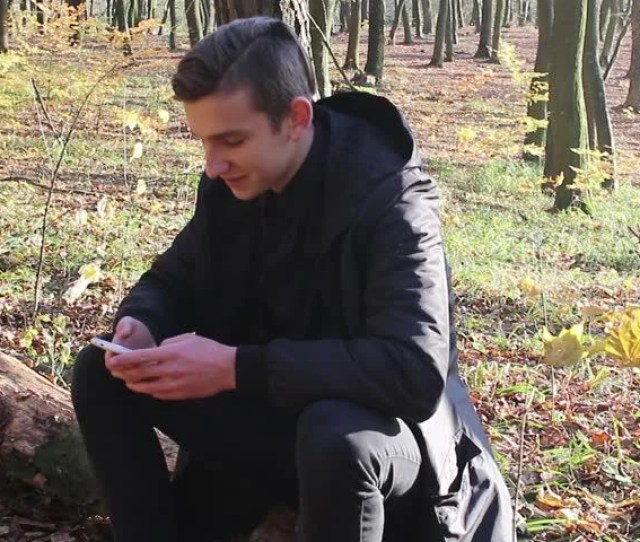 Teenage Boy Using Smart Phone In Forest Handsome Teenager Sitting In Autumn Forest And Playing On Phone