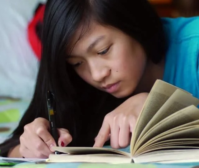 Teen Girl Studying A Close Up Shot Of An Asian Teenage Girl Laying On Her Bed Doing Homework