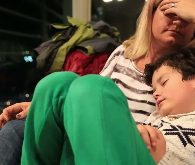Tired Mother And Son Sleeping On The Airport Waiting For Her Flight