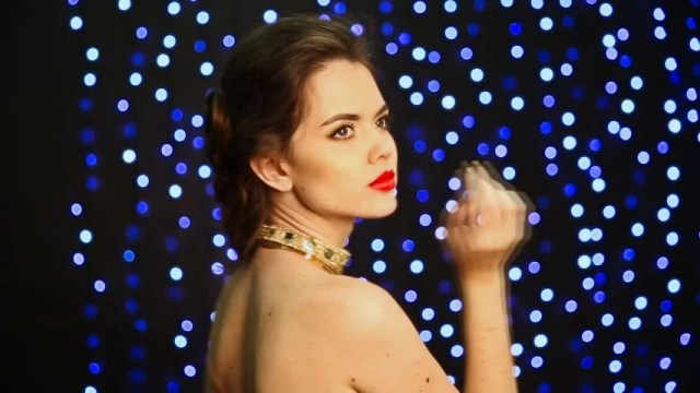 Beautiful Sensual Girl Model With Makeup In Golden Dress And Jewelry Posing Over Holiday Glowing Background In Party Closeup Of Sexy Female With Red Lips
