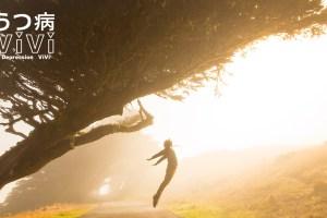 逆光の中大きな木の下で胸を反らし飛び上がる人
