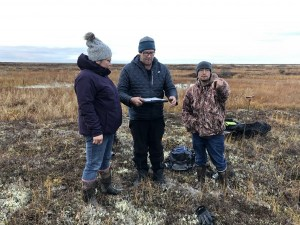 three people stand in a field with scientific equipment