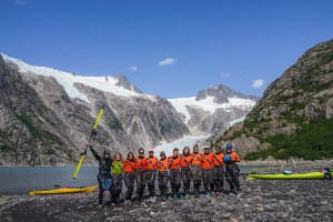 girls in water gear poses in front of mountains and glacier