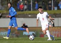England's Phil Foden, right, runs with the ball during the UEFA Nations League soccer match between Iceland and England in Reykjavik, Iceland, Saturday, Sept. 5, 2020. England players Phil Foden and Mason Greenwood have been dropped for Tuesday's game against Denmark after breaching coronavirus rules in Iceland. They will return to England from Reykjavik rather than traveling to Copenhagen on Monday Sept. 7, 2020, after social media video was published in Iceland purporting to show the players meeting women from outside the team bubble. (AP Photo/Brynjar Gunnarson)