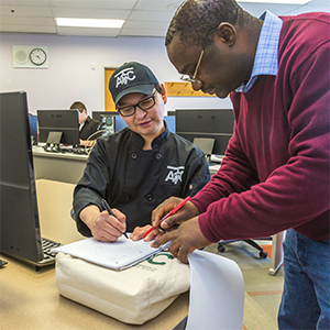 UAF Chukchi Campus Assistant Professor of Developmental Math Kelechukwu Alu works one-on-one with a student during a morning class at the Alaska Technical Center in Kotzebue. (UAF photo)