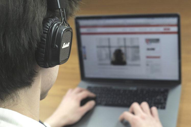 garçon qui écoute la playlist d'Oli du Vendredi #4 avec casque audio et ordinateur
