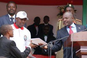 Eddy Munyaneza recevant le Certificat de merite des mains du Chef de l'Etat