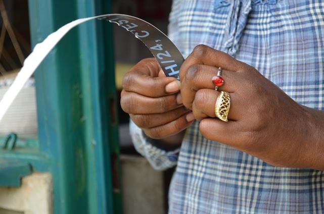 Calénie Nikundanya  en train d'enrouler le petit papier qu'elle va relier après pour avoir un bijou.(www.akeza.net)