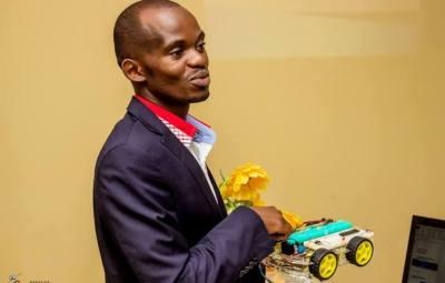 Olfi Kambale Dieudonné avec la voiturette-robot dans la main ©Daniel Luk