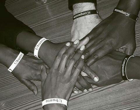 Mains superposées portant des bracelets Ubuntu et Compassion