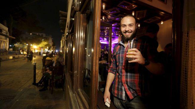 Kenan mosolyogva tart egy pohár italt a kezében a damaszkuszi 80s Bar előtt