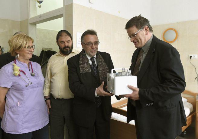 Heisler András, a Mazsihisz elnöke átadja a szövetség ajándékát, egy ultrahangos inhalátor készüléket Velkey Györgynek, a Magyar Református Egyház Bethesda Gyermekkórháza főigazgatójának (Fotó: Bruzák Noémi/MTI)