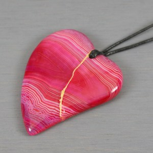 Pink banded agate broken heart pendant with kintsugi repair on black cotton cord