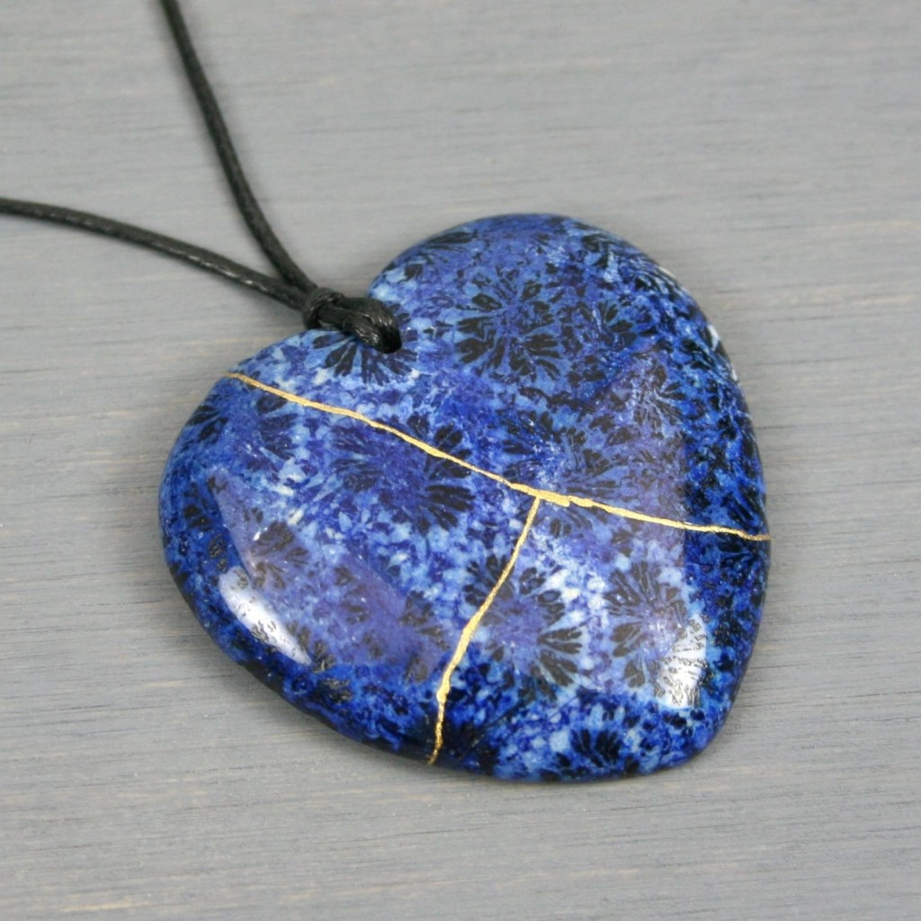 Blue fossil coral broken heart pendant with kintsugi repair on black cotton cord