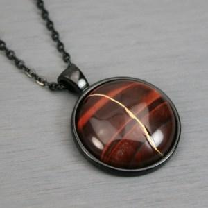 Red tiger eye kintsugi pendant in black setting on chain