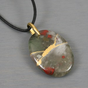 African bloodstone pendant with kintsugi repair on black cotton cord