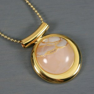 Rose quartz kintsugi pendant in a gold setting on chain
