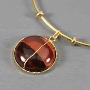 Red tiger eye kintsugi charm on a gold plated bangle bracelet