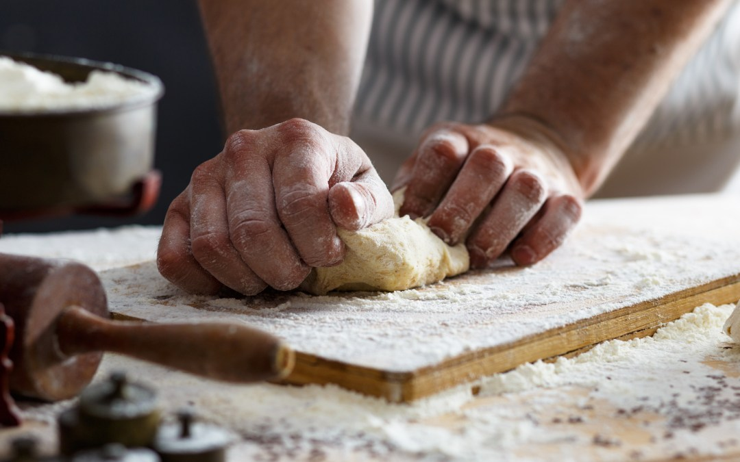 A pair of hands kneading dough to make bread.