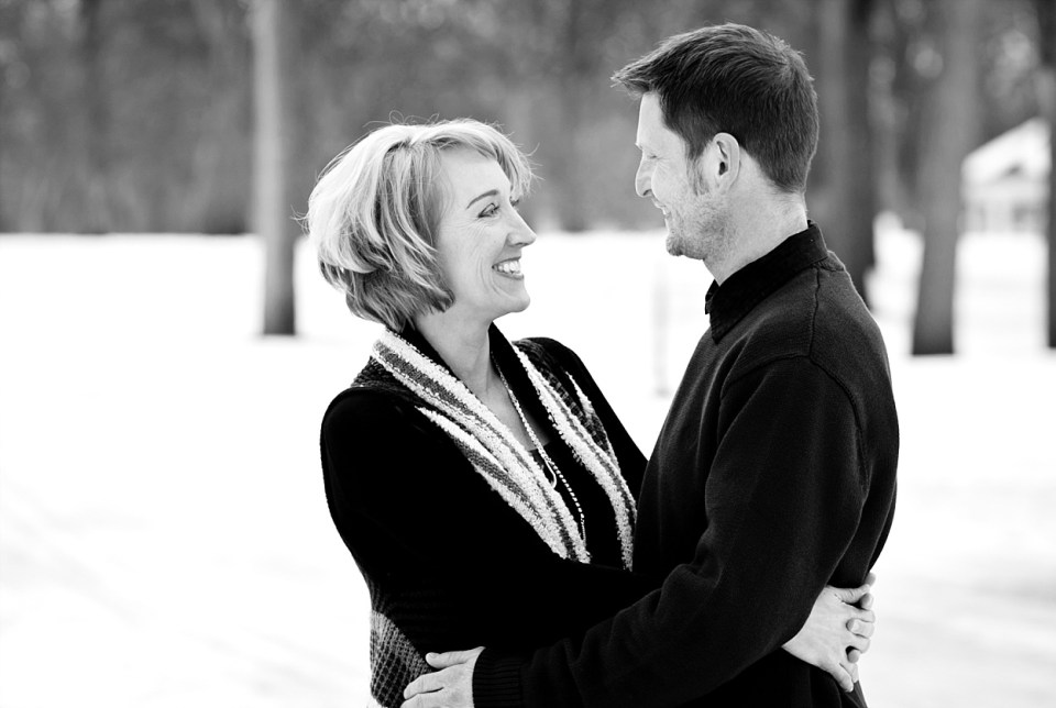 An engagement couple smile while surrounded by snow in Island Park