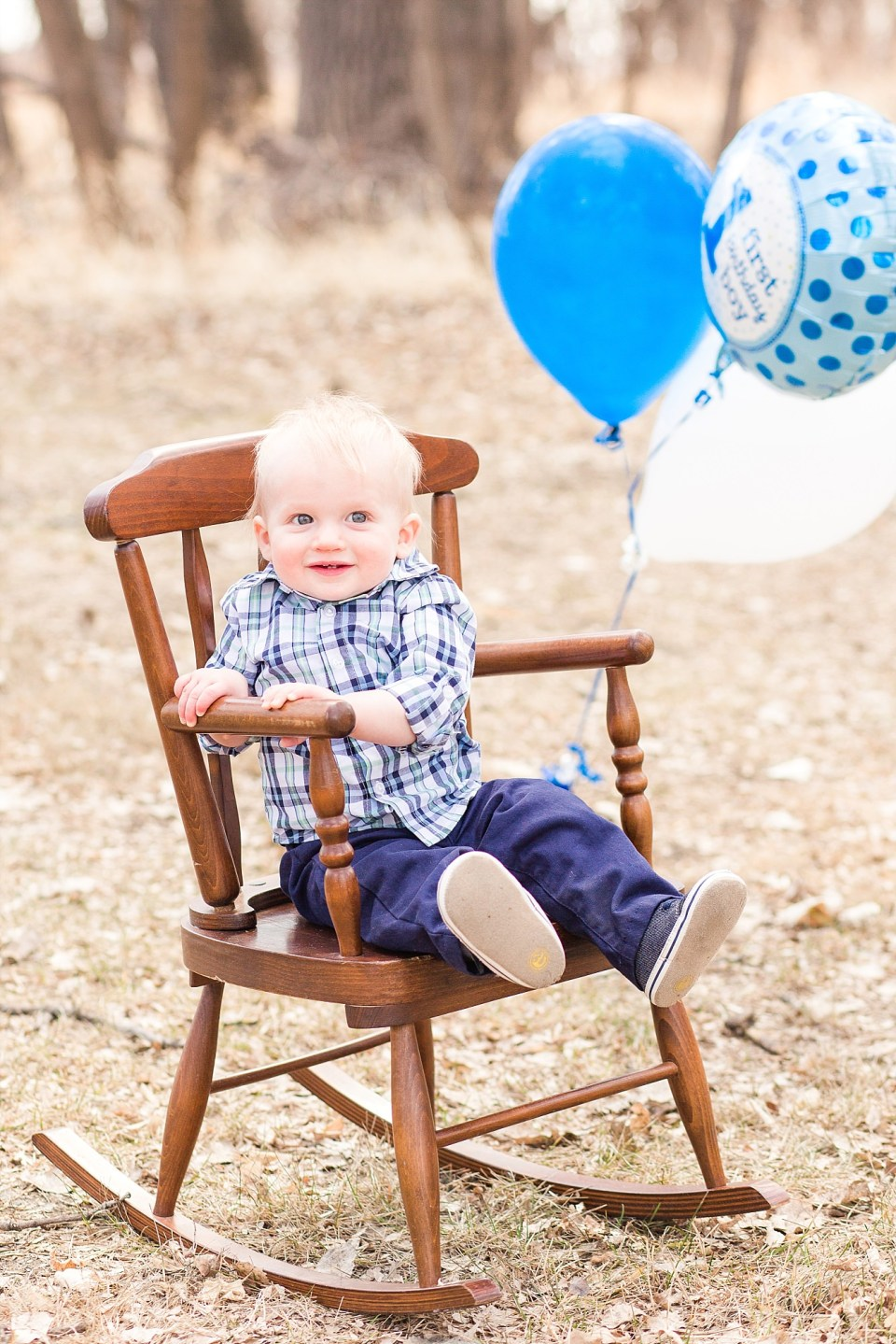 A First Birthday boy sits in a rocking chair with blue balloons blowing in the wind behind him