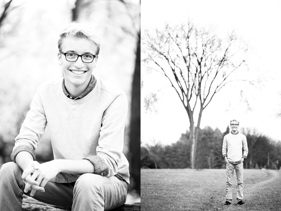 Senior in grey sweater and black glasses stands in front of a large, lone tree in Lindenwood park