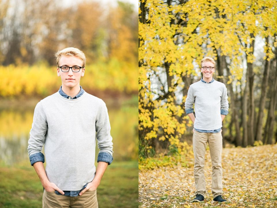 High School Senior in Khakis and a grey sweater stands in front of bright yellow fall leaves