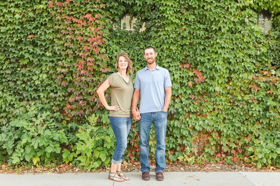 A young couple stand and smile in front of a Downtown Fargo Ivy wall