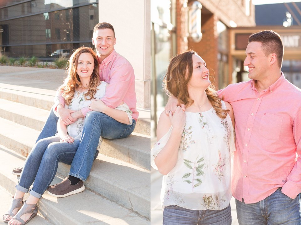 A young couple sit on the stone steps smiling for their engagement session