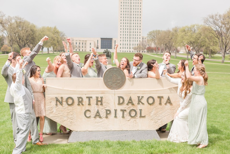 A celebrating bridal party surround the North Dakota Capitol sign