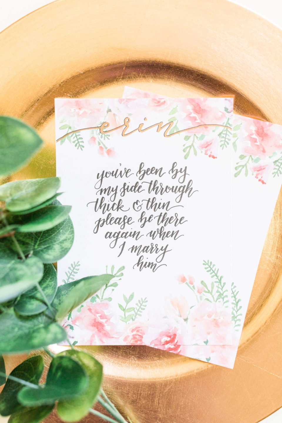 A floral bridal party invite lays on a gold plate with greenery