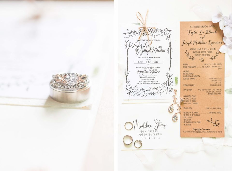 A hand written wedding invitation suite and jewelry on a white table