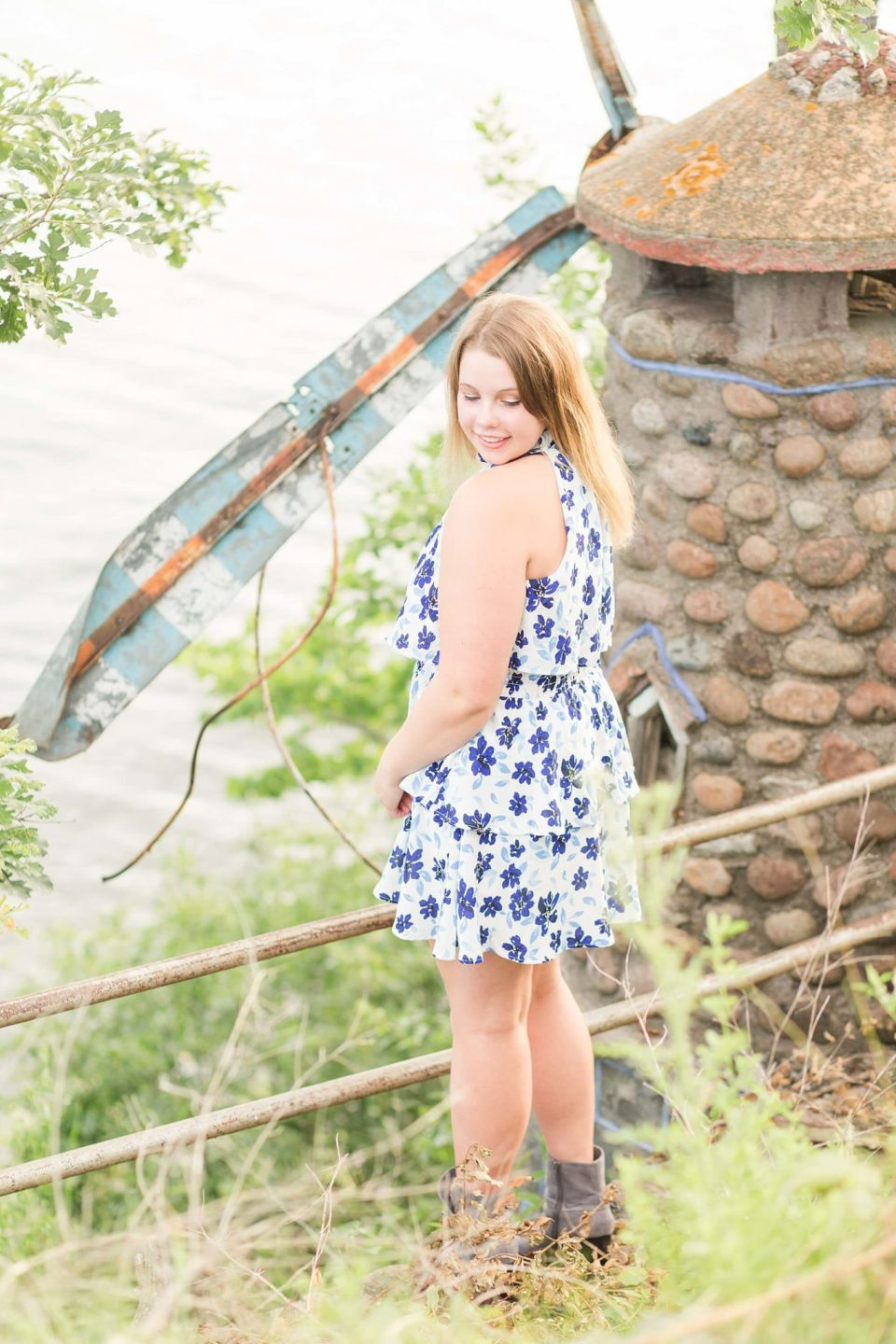 A high school senior smiles down at her floral dress along the lake