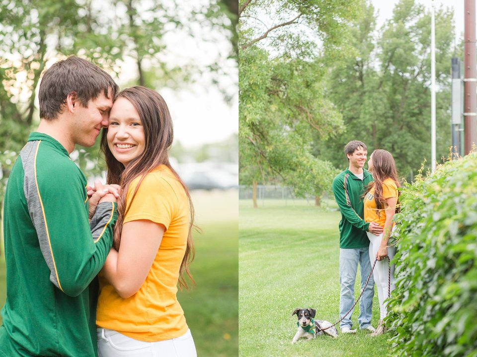 A couple in Bison gear smile and embrace during their engagement session with a puppy