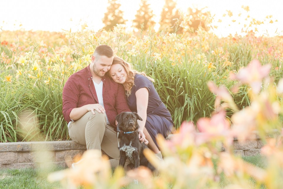 An engaged couple and their dog enjoy the sunset at the NDSU flower garden