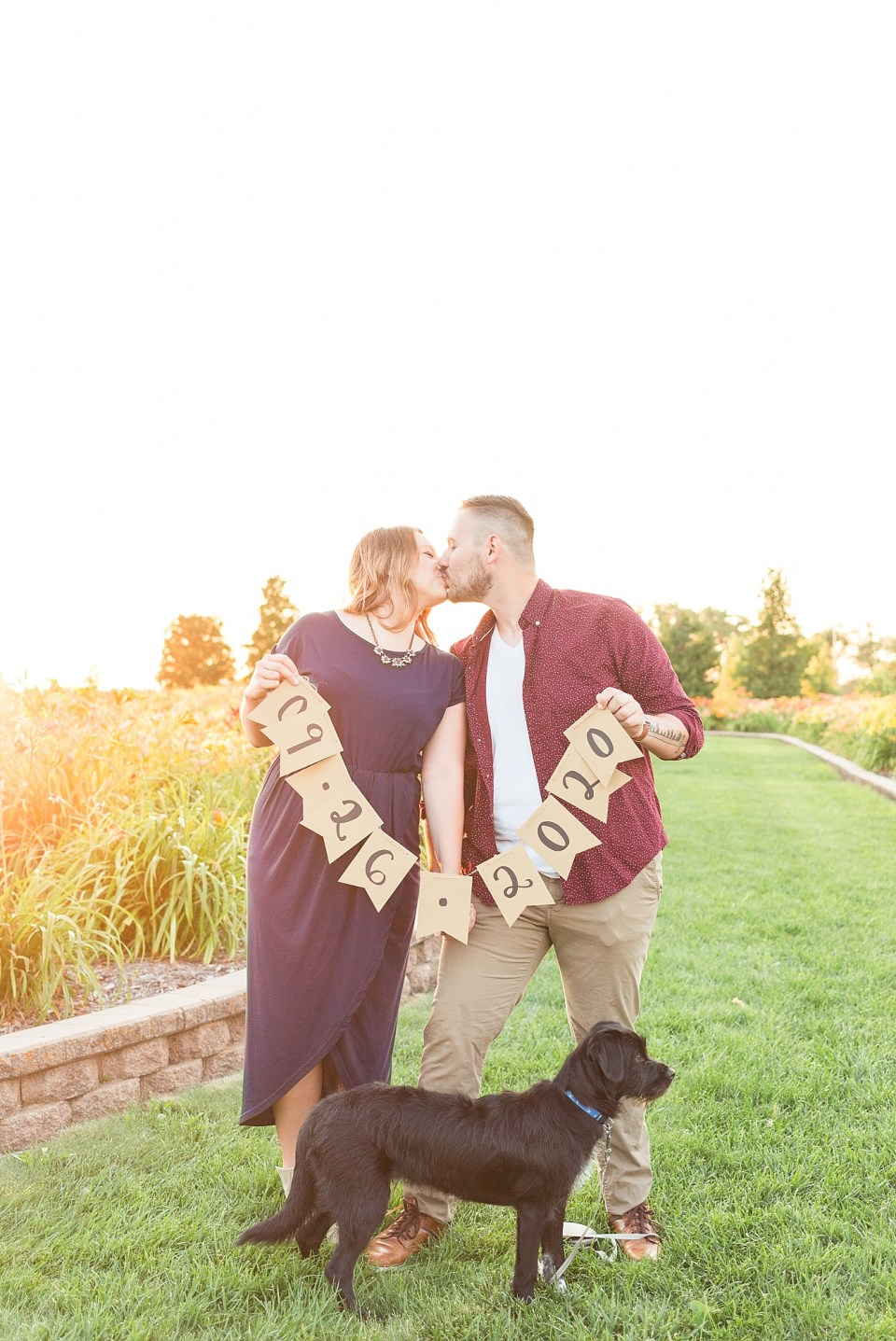 A couple kisses and holds a banner with their engagement date printed