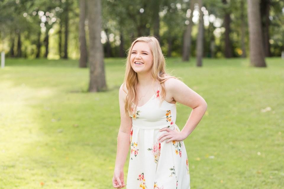 Senior girl laughs in white floral dress in Oak Grove Park, Fargo, ND