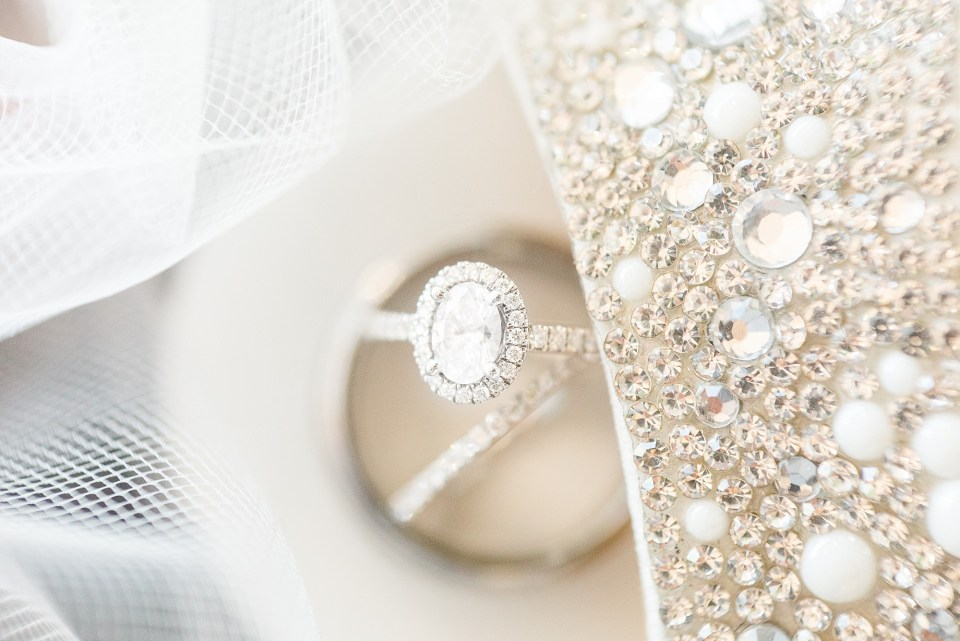 Wedding day details with diamond ring with a halo and sparkly shoes.